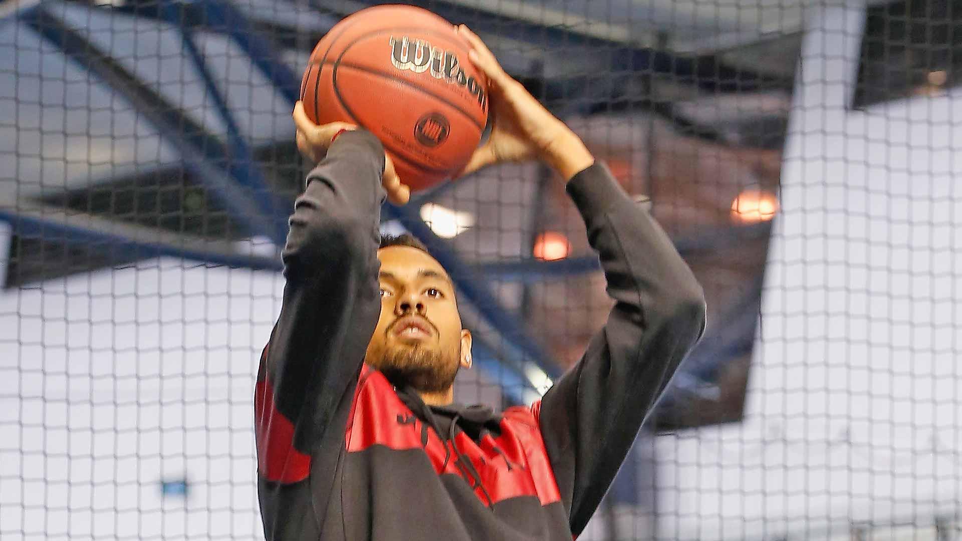 <a href='https://www.atptour.com/en/players/nick-kyrgios/ke17/overview'>Nick Kyrgios</a> shoots a basketball