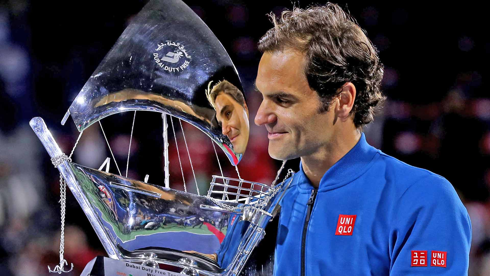 Roger Federer looks at his 100th tour-level trophy.