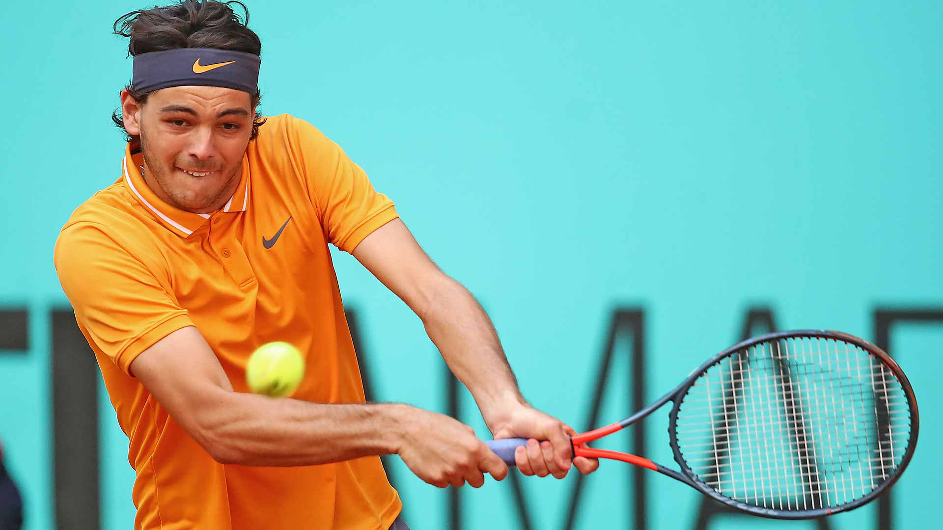 <a href='https://www.atptour.com/en/players/taylor-fritz/fb98/overview'>Taylor Fritz</a> hits a backhand in Madrid
