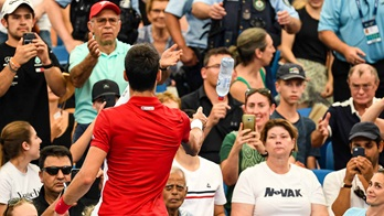 Novak Djokovic helps a fan during the third set of his ATP Cup quarter-final match against Denis Shapovalov on Thursday.