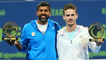 Rohan Bopanna and Wesley Koolhof lift their trophies after winning the Qatar ExxonMobil Open on Friday.