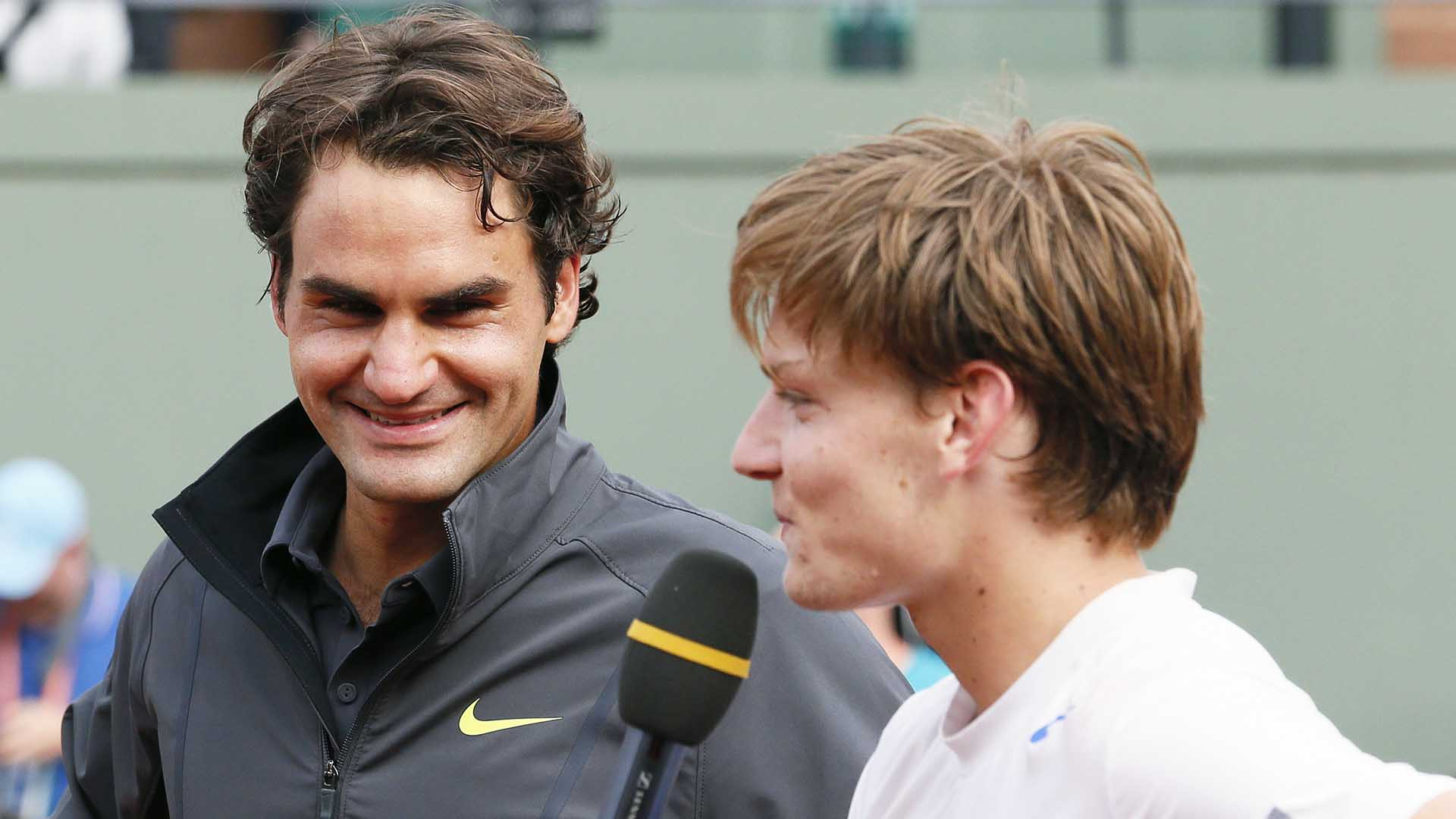 Roger Federer and David Goffin share a joint on-court interview after their 2012 Roland Garros Round of 16 match on Court Suzanne-Lenglen.